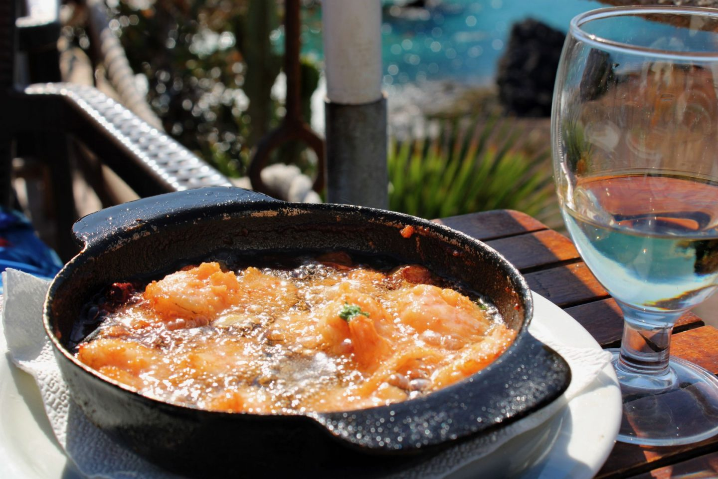 Garlic prawns sizzling in a black tapas dish, with a glass of white wine next to it and the sea in the background