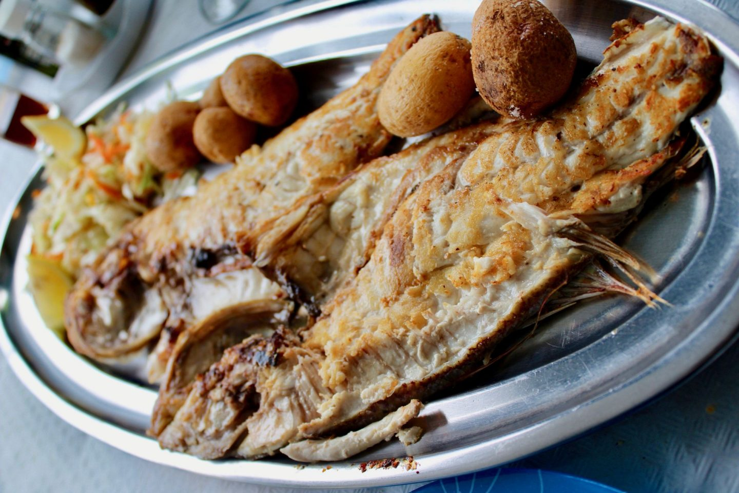 A plate of fish eaten at Los Gallegos in Orzola, Lanzarote. It's a long metal plate, with the front in focus and the back fading out of focus.