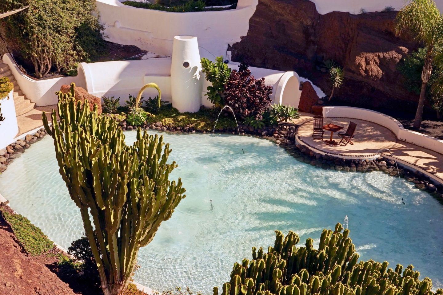 Museo Lagomar, one of the things to do in Lanzarote. Image shows a swimming pool surrounded by trees and plants, with white walls in the background and a small, circular patio.