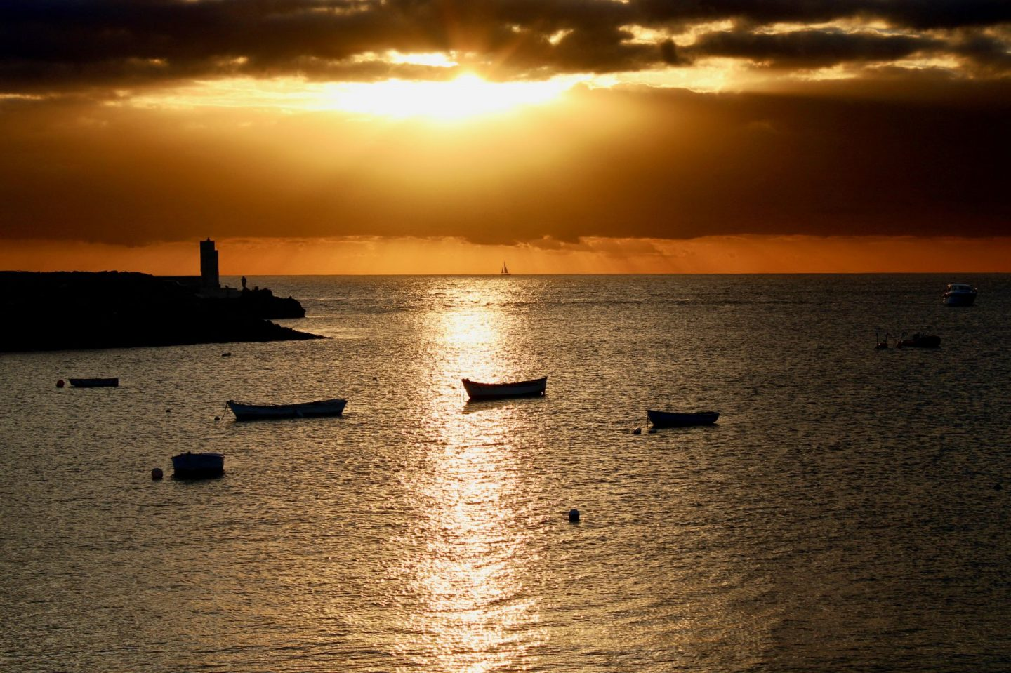 A sunset from El Mirador in Playa Blanca, showing a view out of the sea with the sun shining through the clouds and creating a reflection on the water