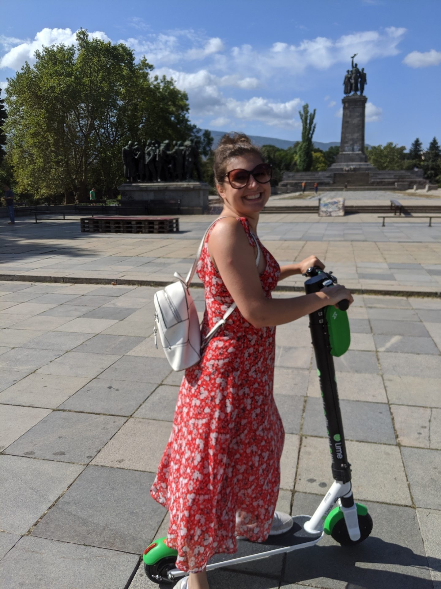 Nell on an electric scooter in Sofia. She's smiling at the camera and wearing a flowing red, floral dress