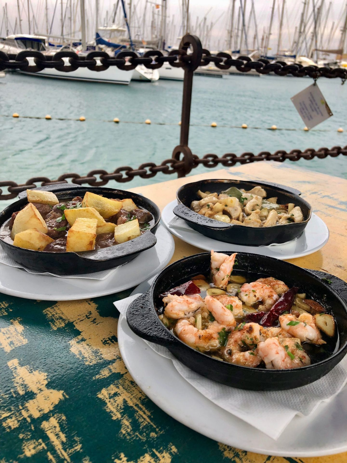 Three plates of tapas, served in black dishes. Shows garlic prawns, garlic chicken and beef stew. In the background you can see Playa Blanca Marina.