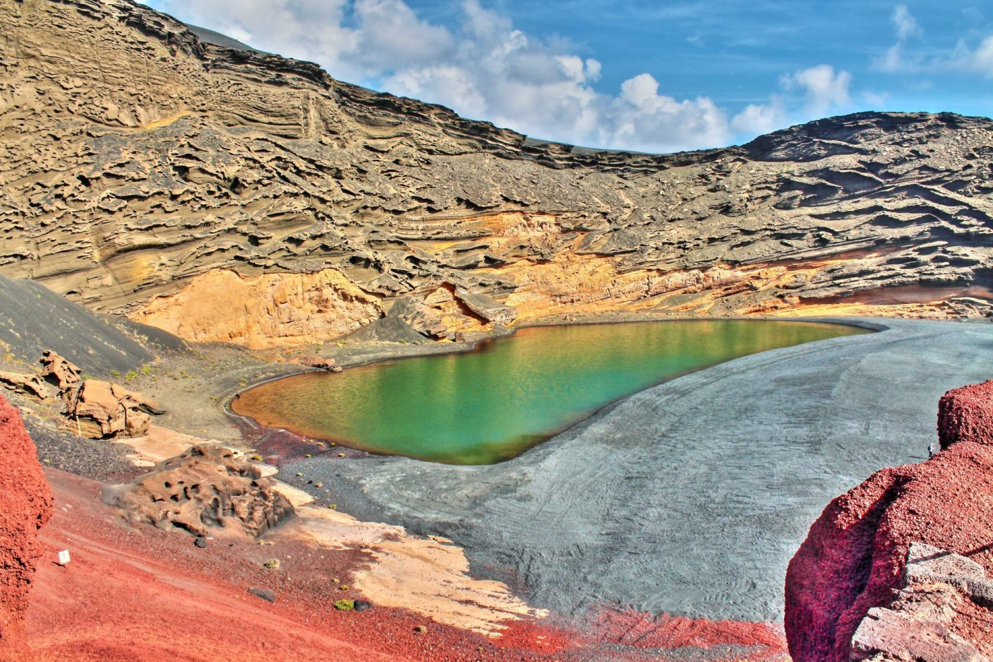 El Lago Verde near El Golfo in Lanzarote. Image shows a green within a volcanic crater, surrounded by black sand.
