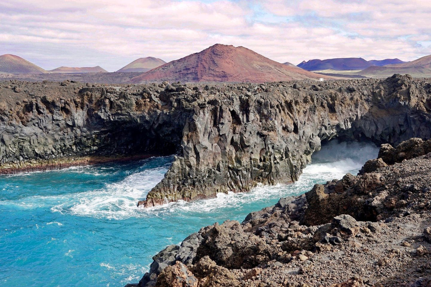 Los Hervideros in Lanzarote, showing the sea smashing against black rock, with a volcanic hill in the background