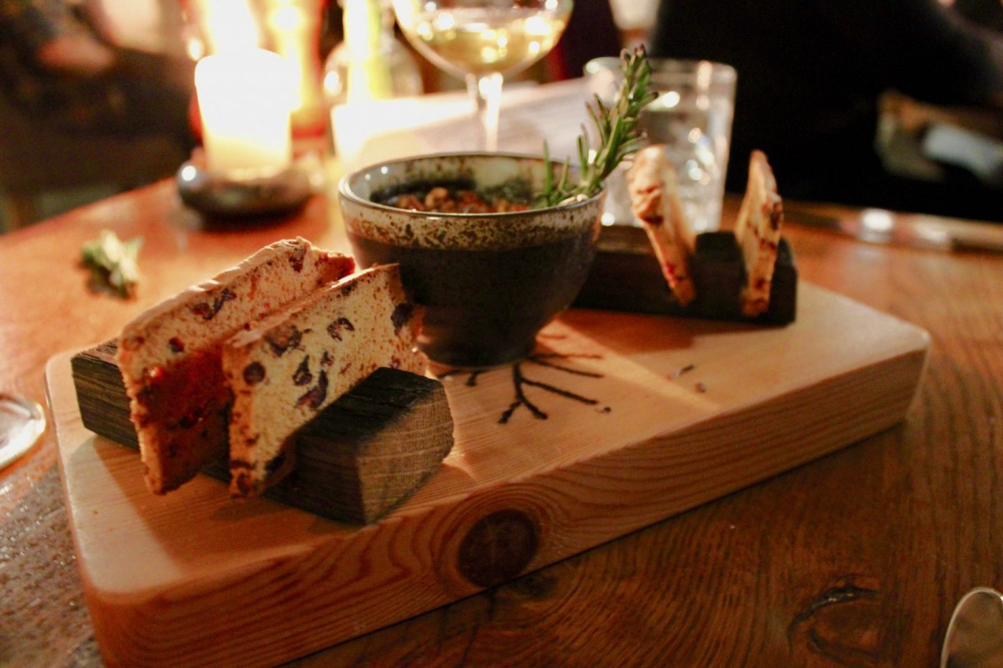 A bowl of baked cheese with a sprig of rosemary on top, served on a wooden board at the Star Inn at Harome