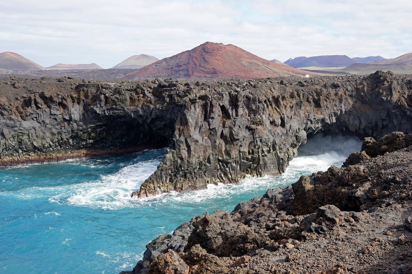 Things to do in Lanzarote: los hervideros showing the sea crash up against black rock cliffs