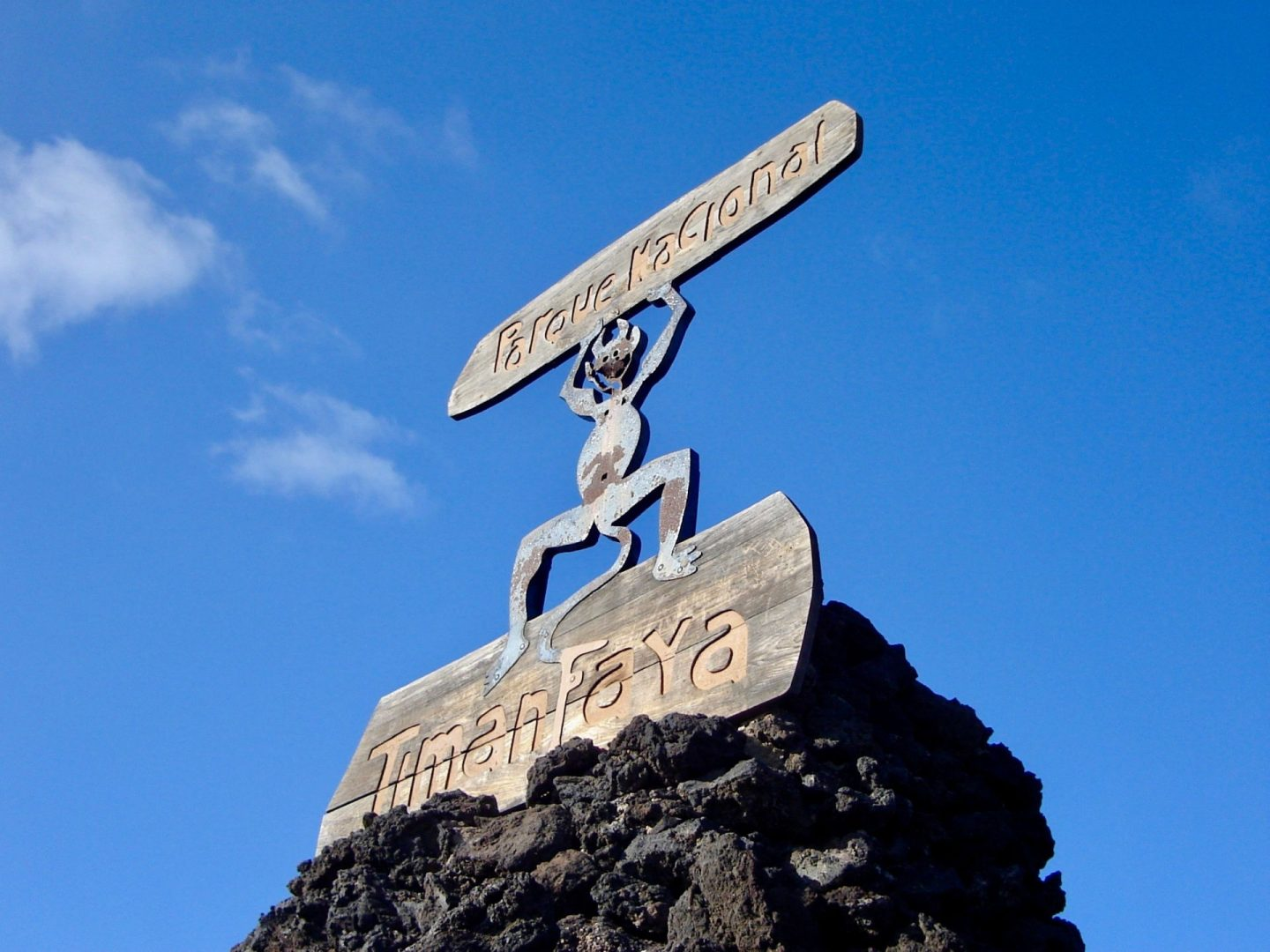 Things to do in Lanzarote: a wooden sign for Timanfaya national park, on top of black rock and against a clear blue sky