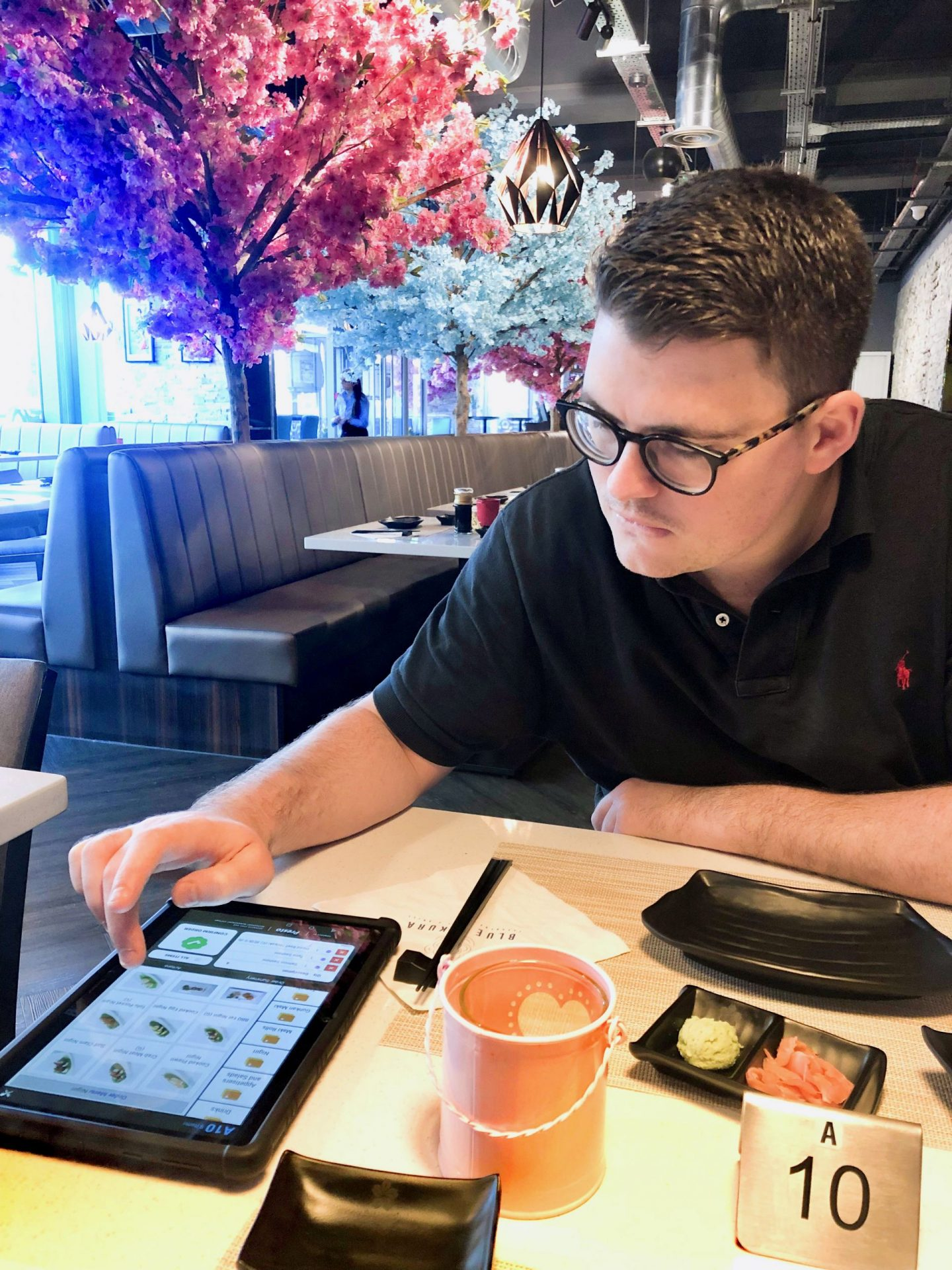 Nell's boyfriend Billy ordering food on a tablet at Blue Sakura Leeds. He's concentrating and slightly biting his lip in anticipation.