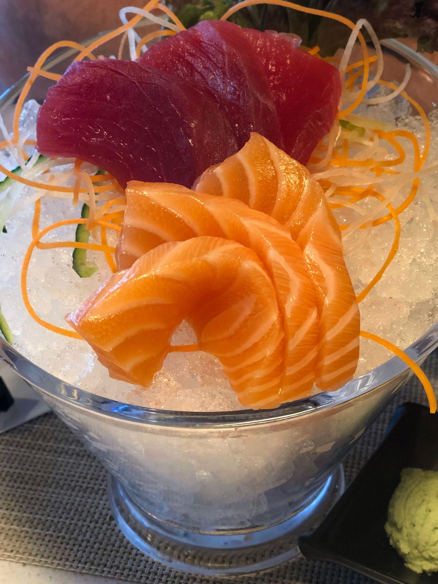 Salmon and Tuna sashimi sat on top of ice at Blue Sakura Leeds. The image is a close up and the colours are vibrant, the fish looks very fresh.