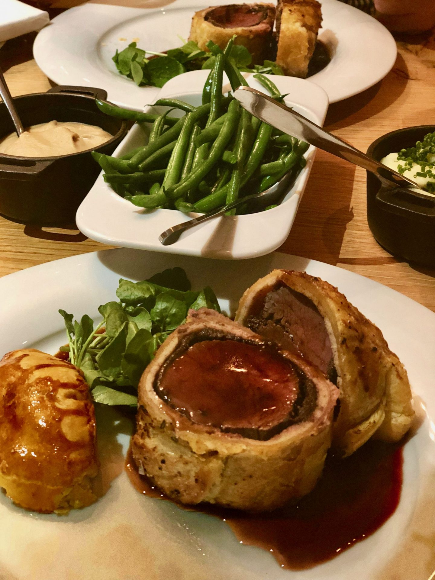 Dinner at the black swan helmsley. A white round plate contains two thich slices of beef wellington with a rich gravy poured over the top. Behind that is a dish of green beans, of mash and of celeriac puree, each with a spoon.