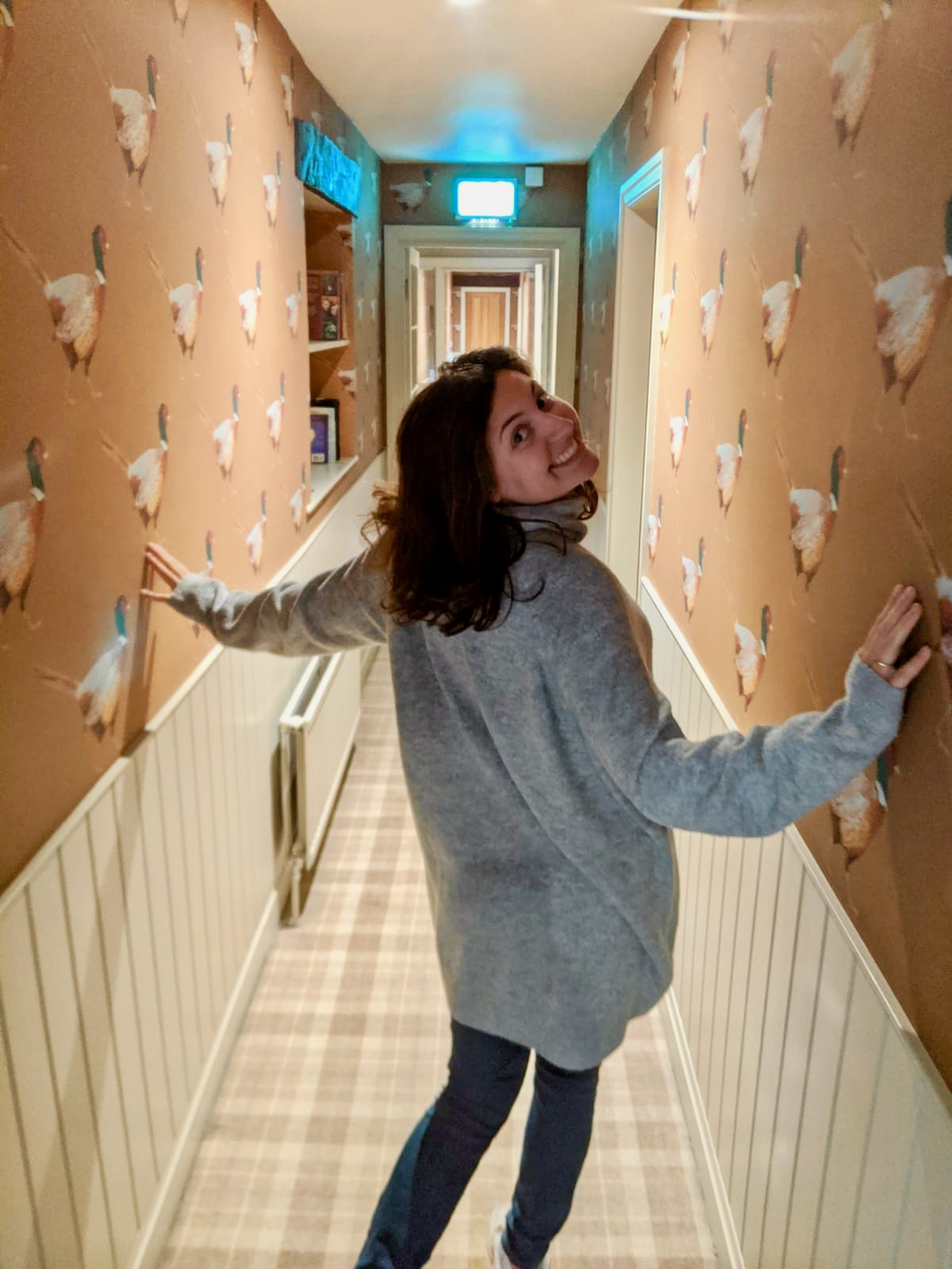 Nell posing in the corridor with pheasant wallpaper. She's walking away from the camera but turning to smile back at it.
