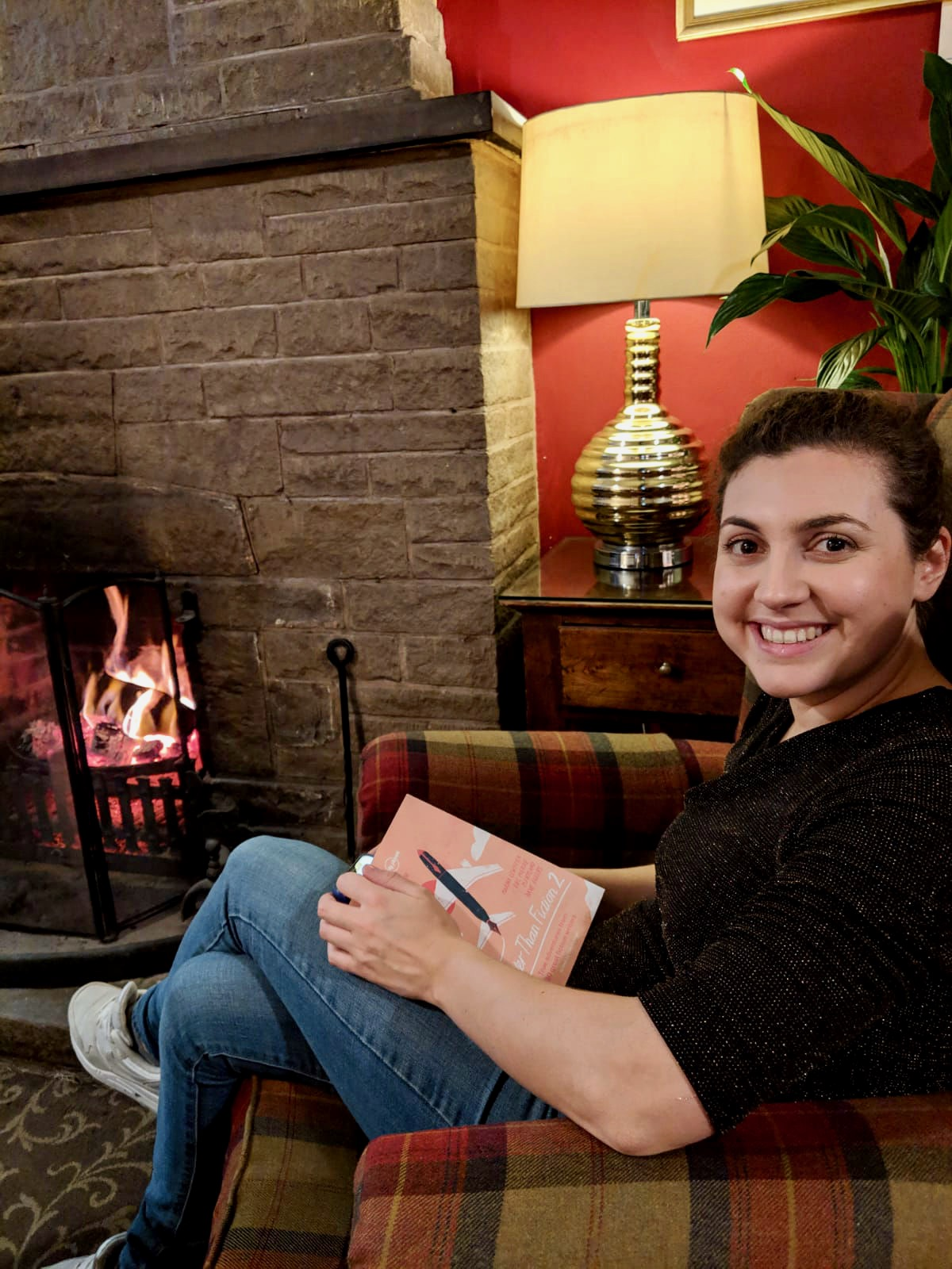 Nell sat in a chequered armchair next to a log fire, holding a book in her lap and smiling at the camera