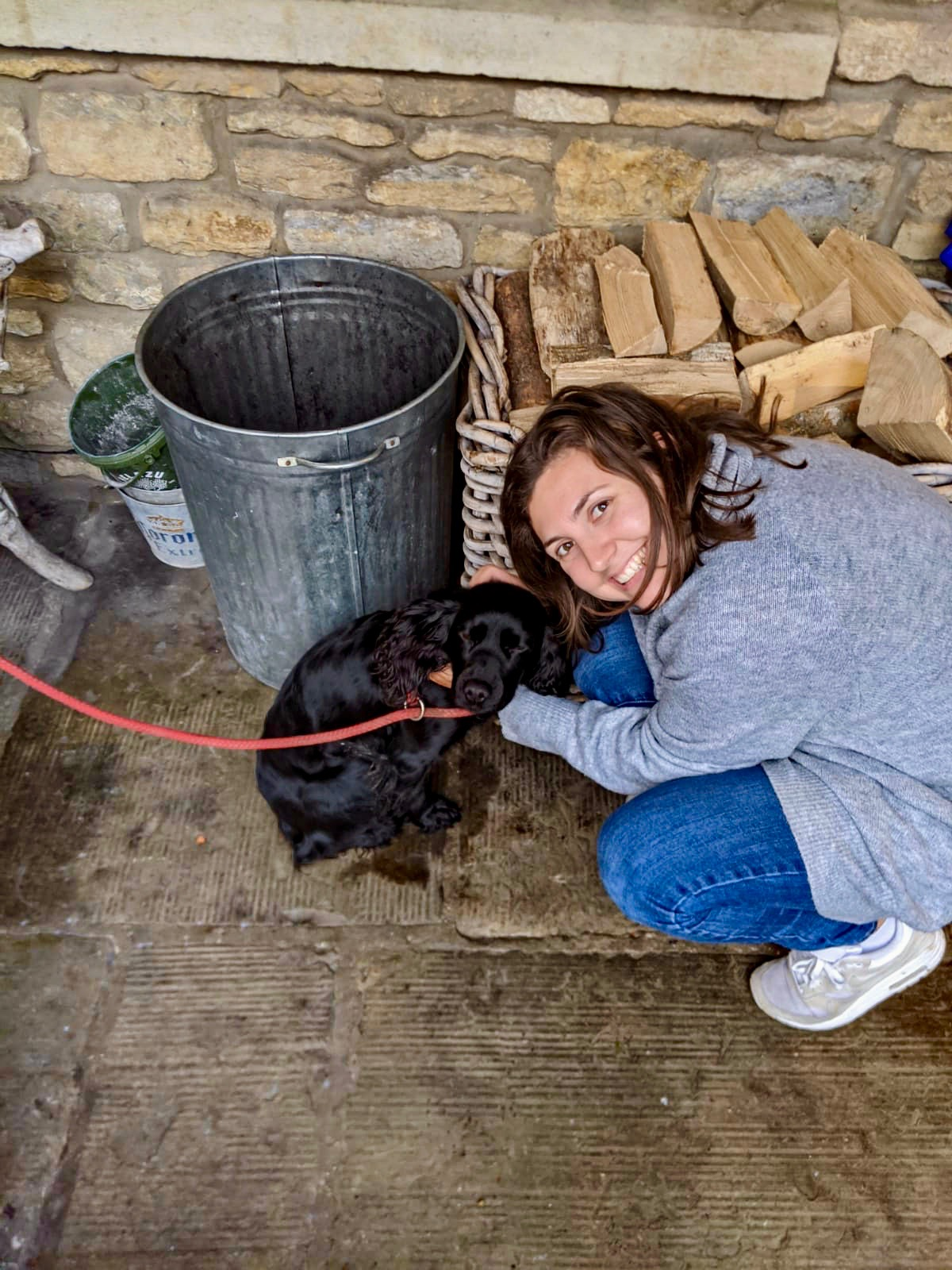 Nell crouching down outside the pheasant hotel Harome stroking a dark brown spaniel puppy. Nell and the puppy are both looking up at the camera and smiling.