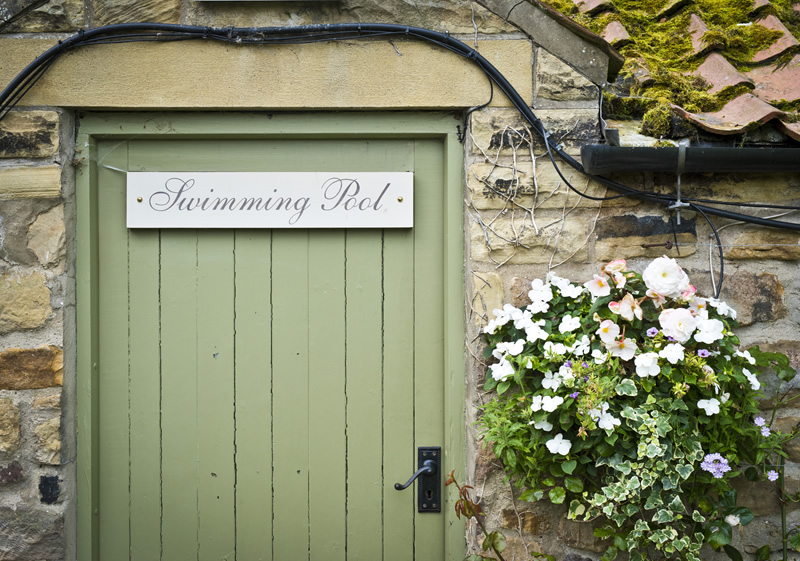 The Pheasant Hotel Harome: Green door with a sign for the swimming pool and a hanging basket