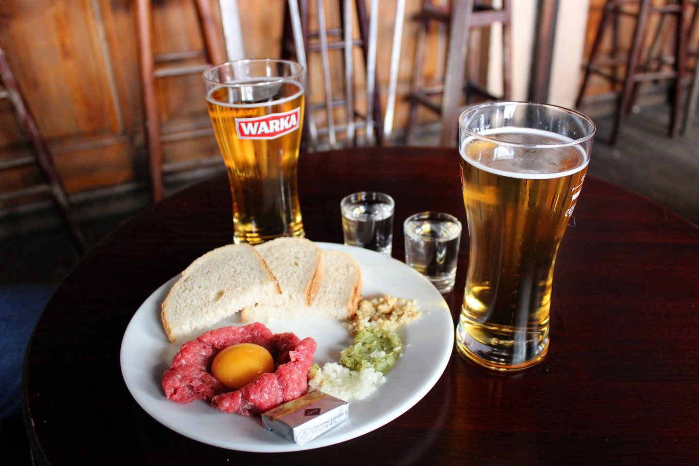 best bars and restaurants in wroclaw - a white plate of beef tartare with two beers and two vodkas either side