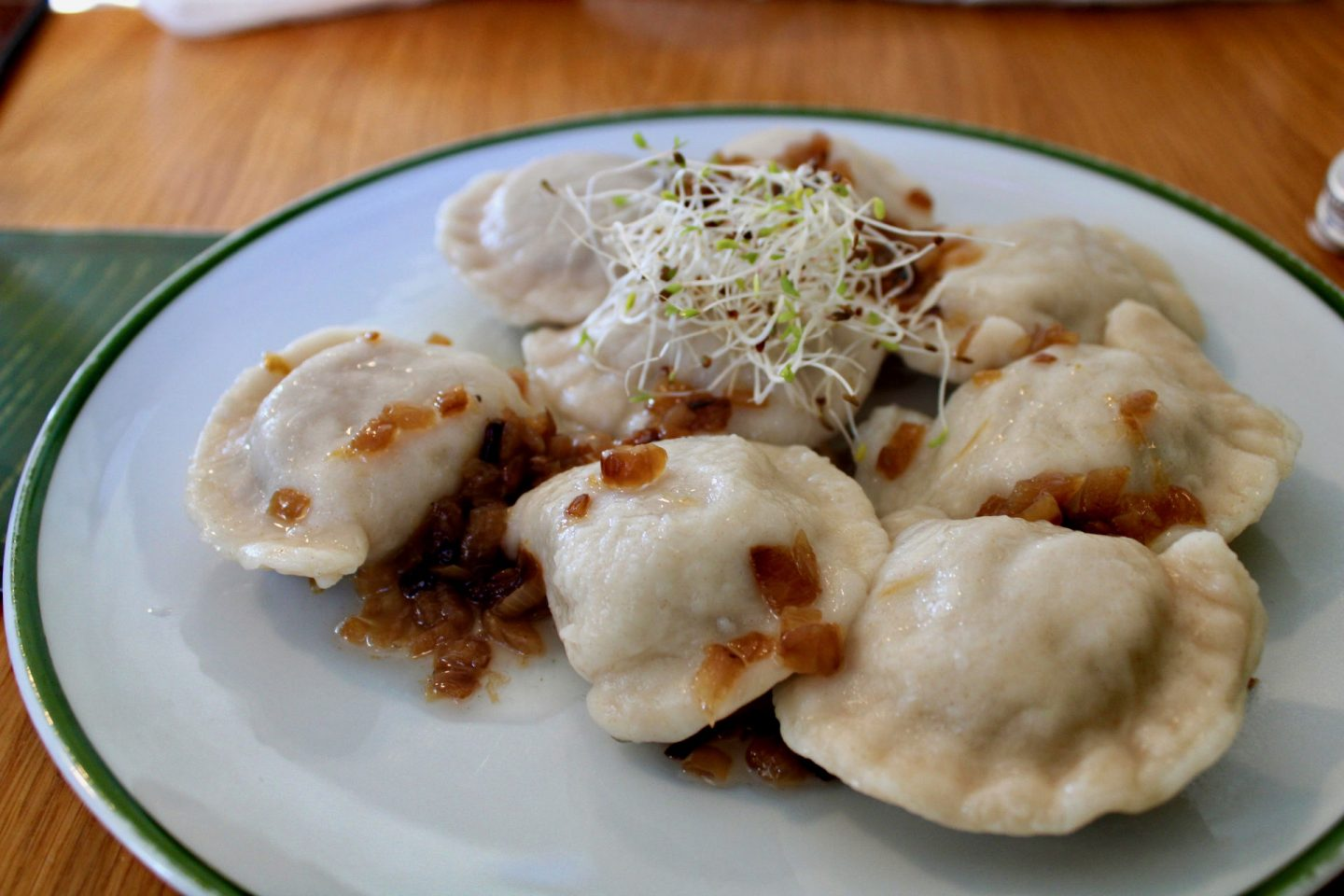 best restaurants in wroclaw - a plate of pierogis on a white plate, with garnish on top