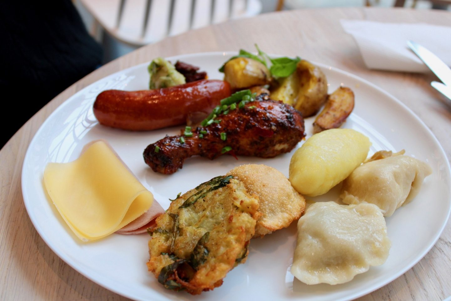 best bars restaurants in wroclaw - lepione. A large white plate showing a random selection of dumpling, chicken wing, potatoes and sausage