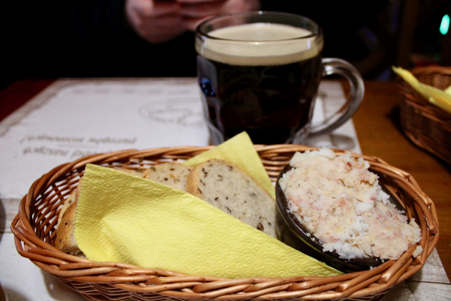 best bars restaurants wroclaw - bread topped with lard in a bread basket, with beer in the background