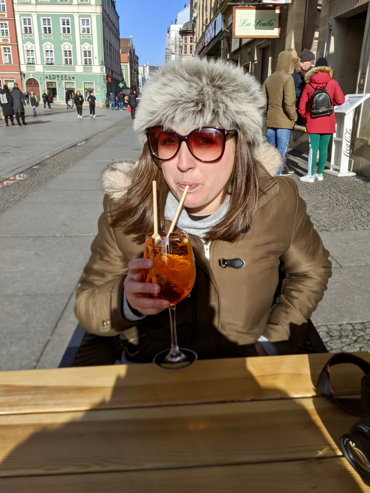 cheap european city break - Nell drinking an Aperol Spritz in the market square in Wroclaw, Poland, whilst wrapped up in a coat and a fluffy hat trying to stay warm.
