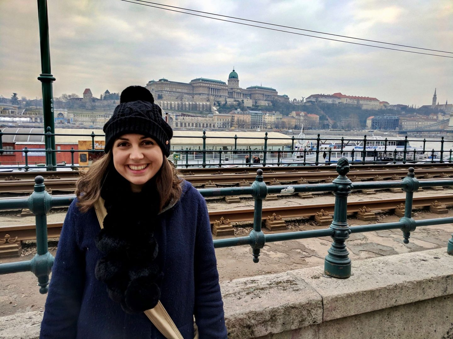 cheap european city break - Nell in Budapest, with the tramline, river and castle buildings behind her