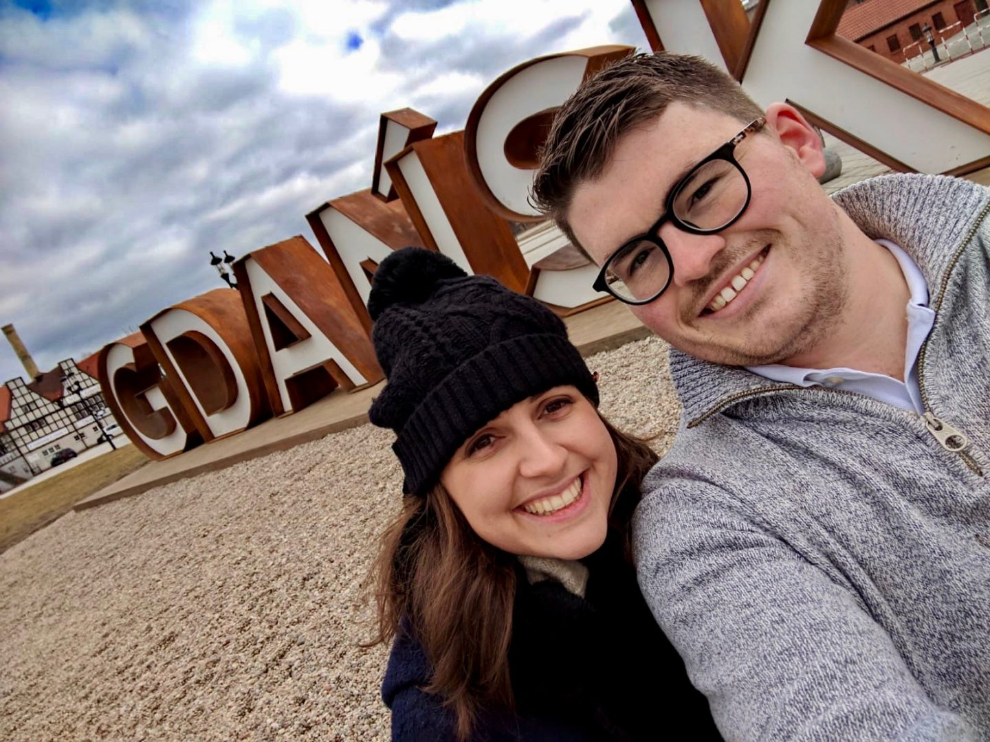 cheap european city break - Nell and boyfriend in Gdansk standing in front of a giant gdansk sign and smiling