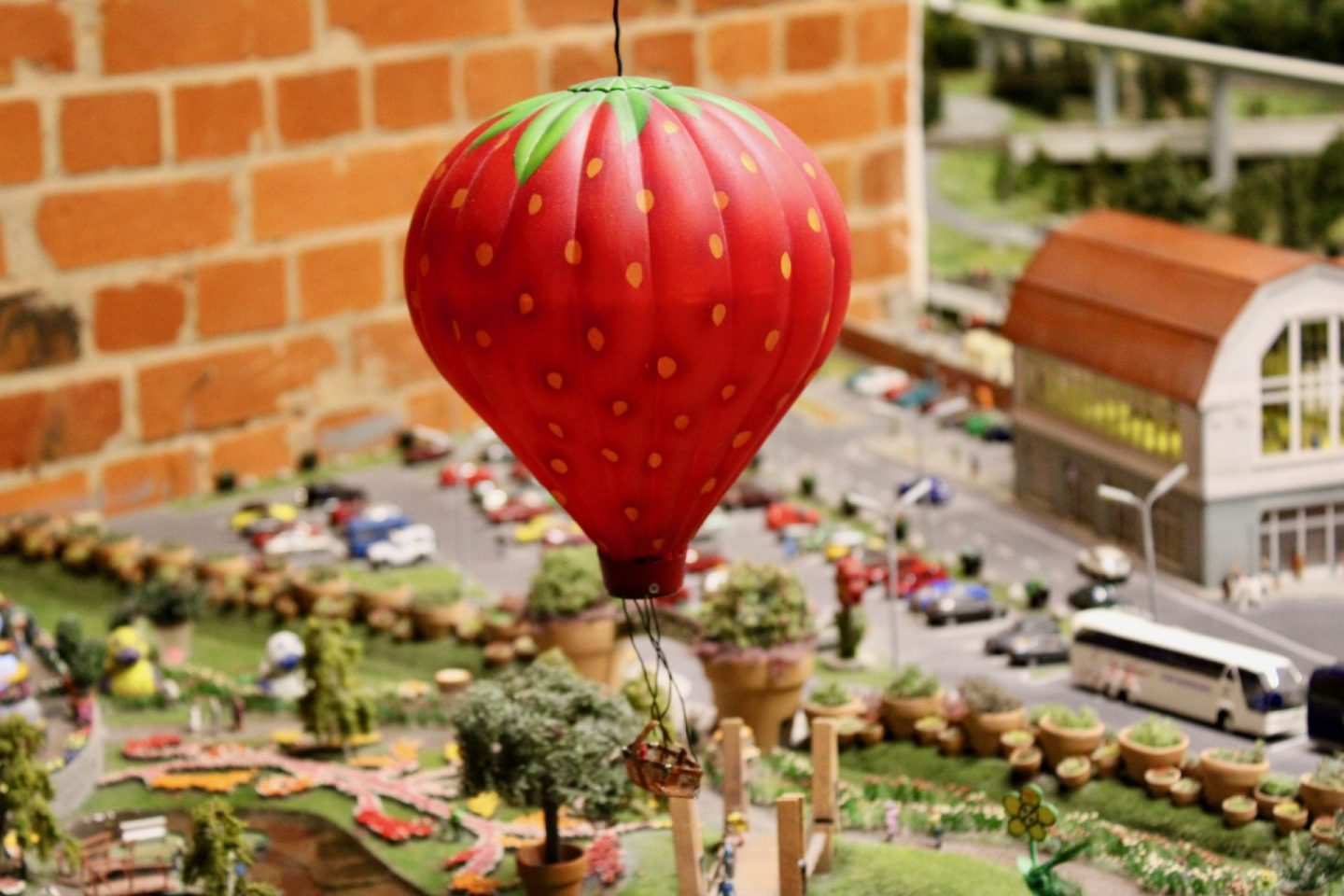 cheap european city break - inside minatur wunderland model railway museum. Image shows a strawberry hot air balloon floating over Hamburg
