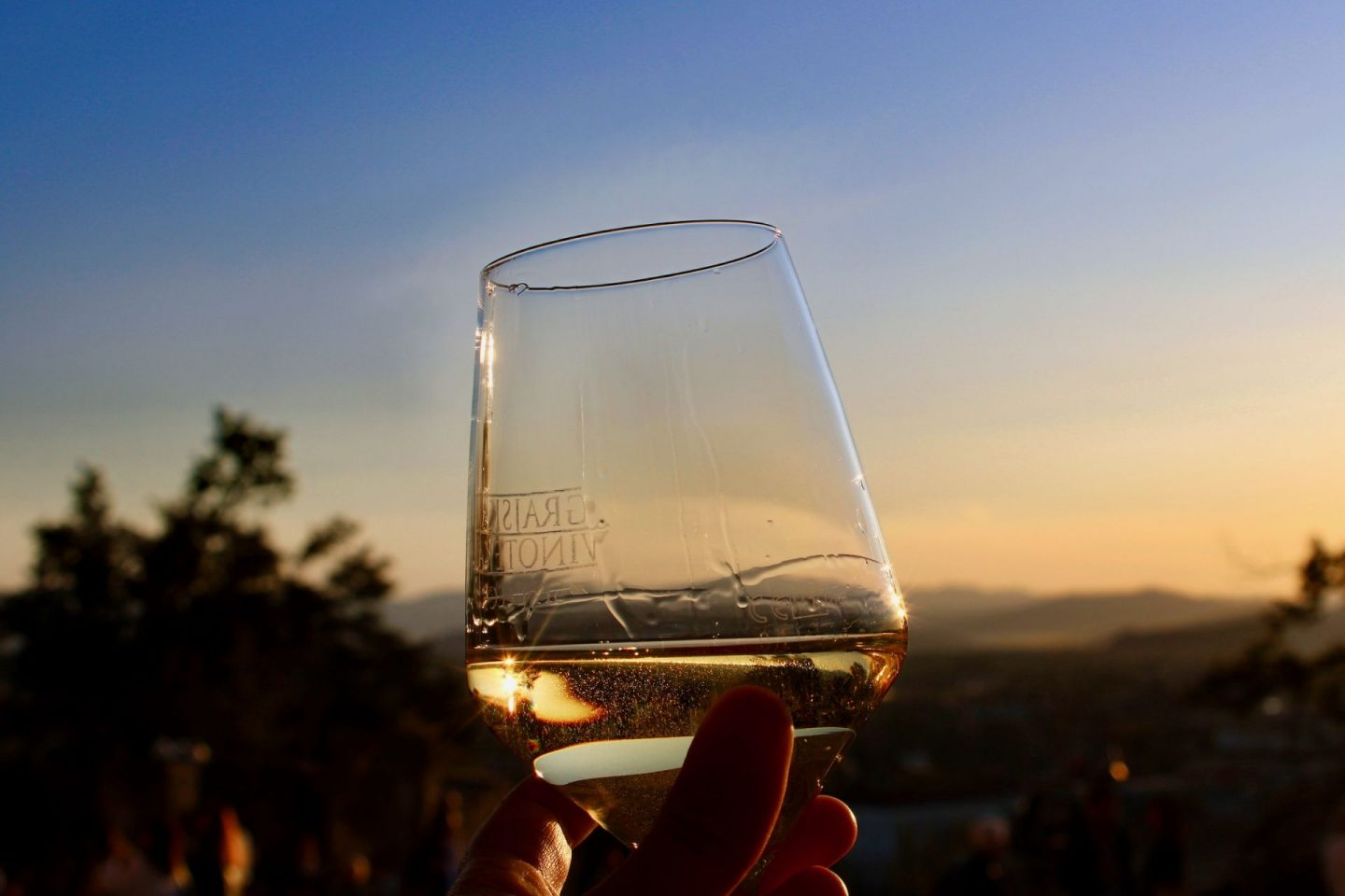cheap european city break - a glass of white wine being held up with the sunset behind, a view from the castle in Ljubljana