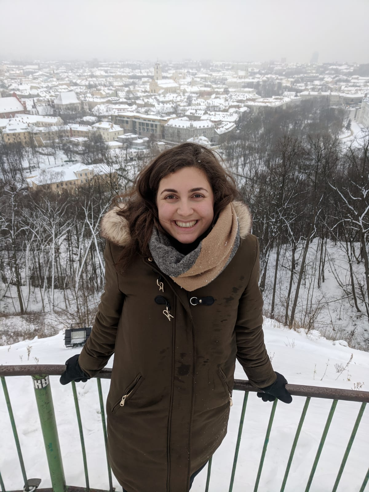 cheap european city break - Nell in snowy Vilnius, smiling at the camera at the top of a hill with the snowy city below.