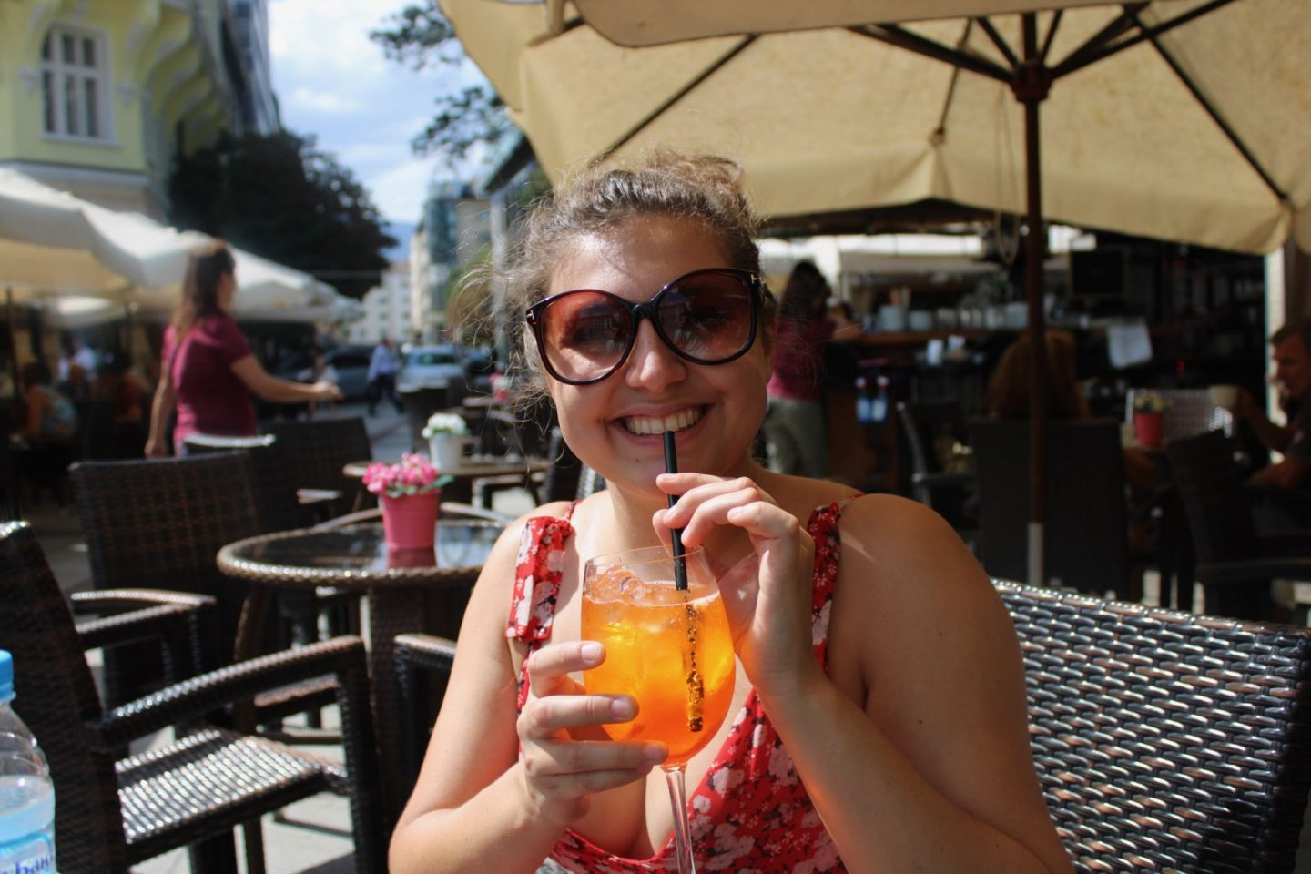 cheap european city break - Nell drinking an Aperol Spritz in Sofia, Bulgaria. She's wearing sunglasses, a red dress and smiling at the camera