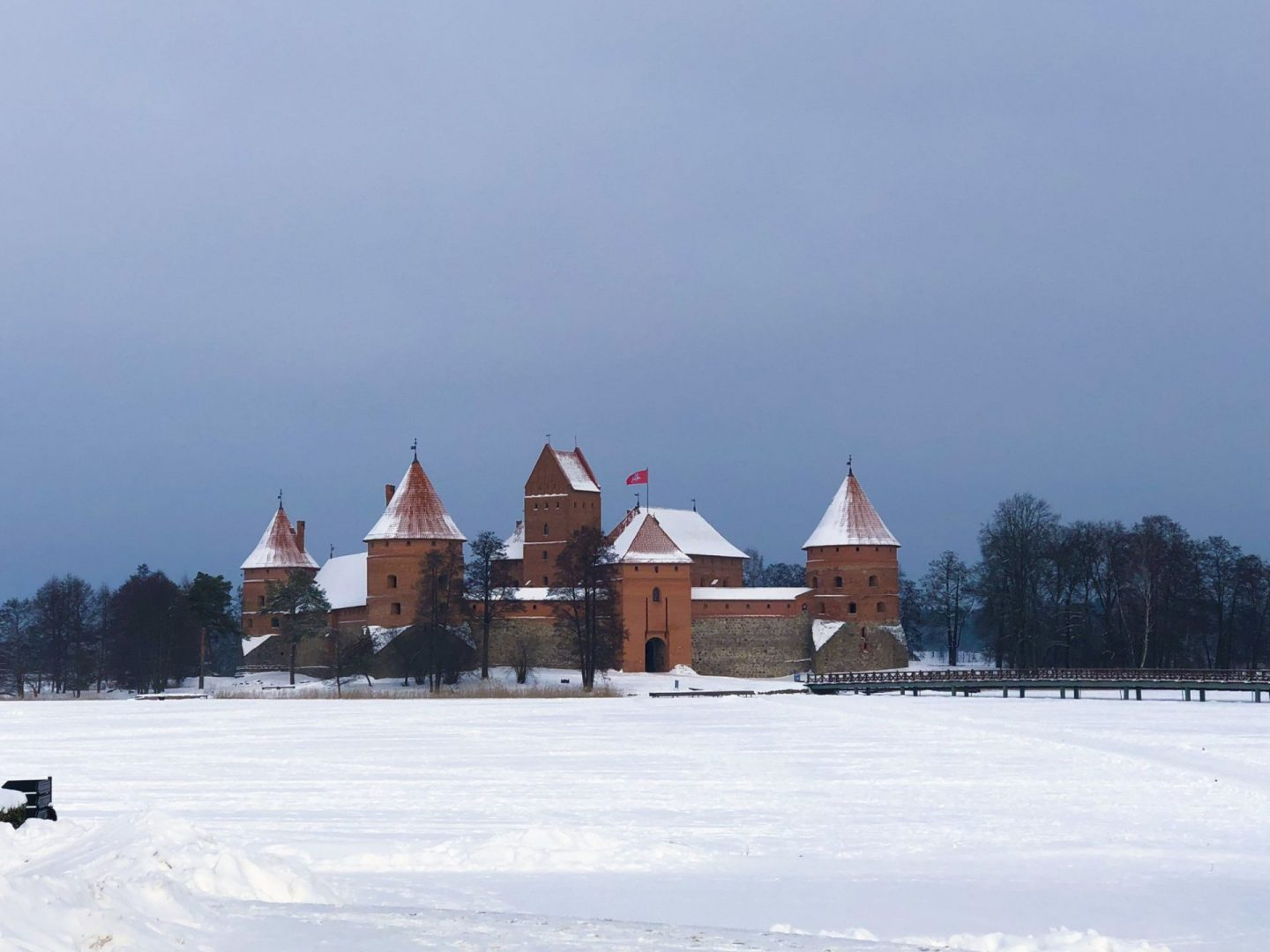 cheap european city break - Trakai castle in Trakai near Vilnius in Lithuania. The lake around the castle is frozen and covered in snow, and the sky is a moody grey