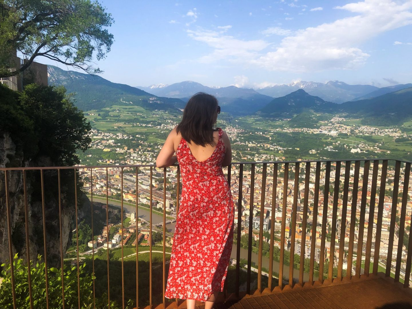cheap european city break - Nell at the top of the cable car in Trento, Trentino, facing away from the camera and admiring the views of the town below and the mountains in the background. She's wearing a red flowing dress.