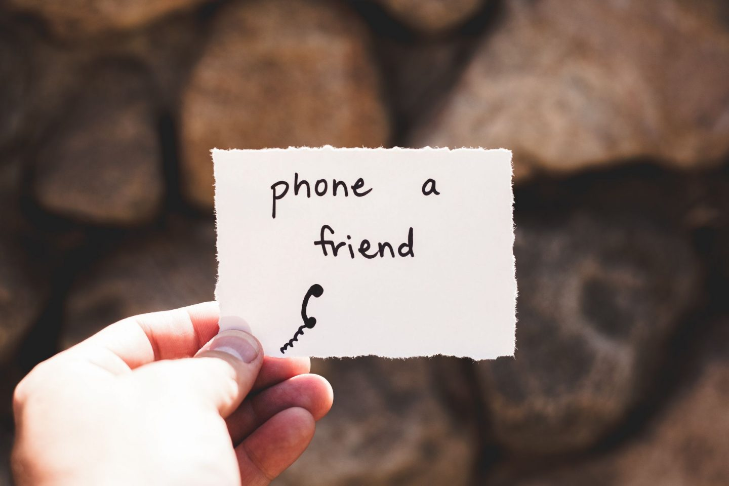 mental health during coronavirus - a hand holding a small piece of paper with 'phone a friend' written on it