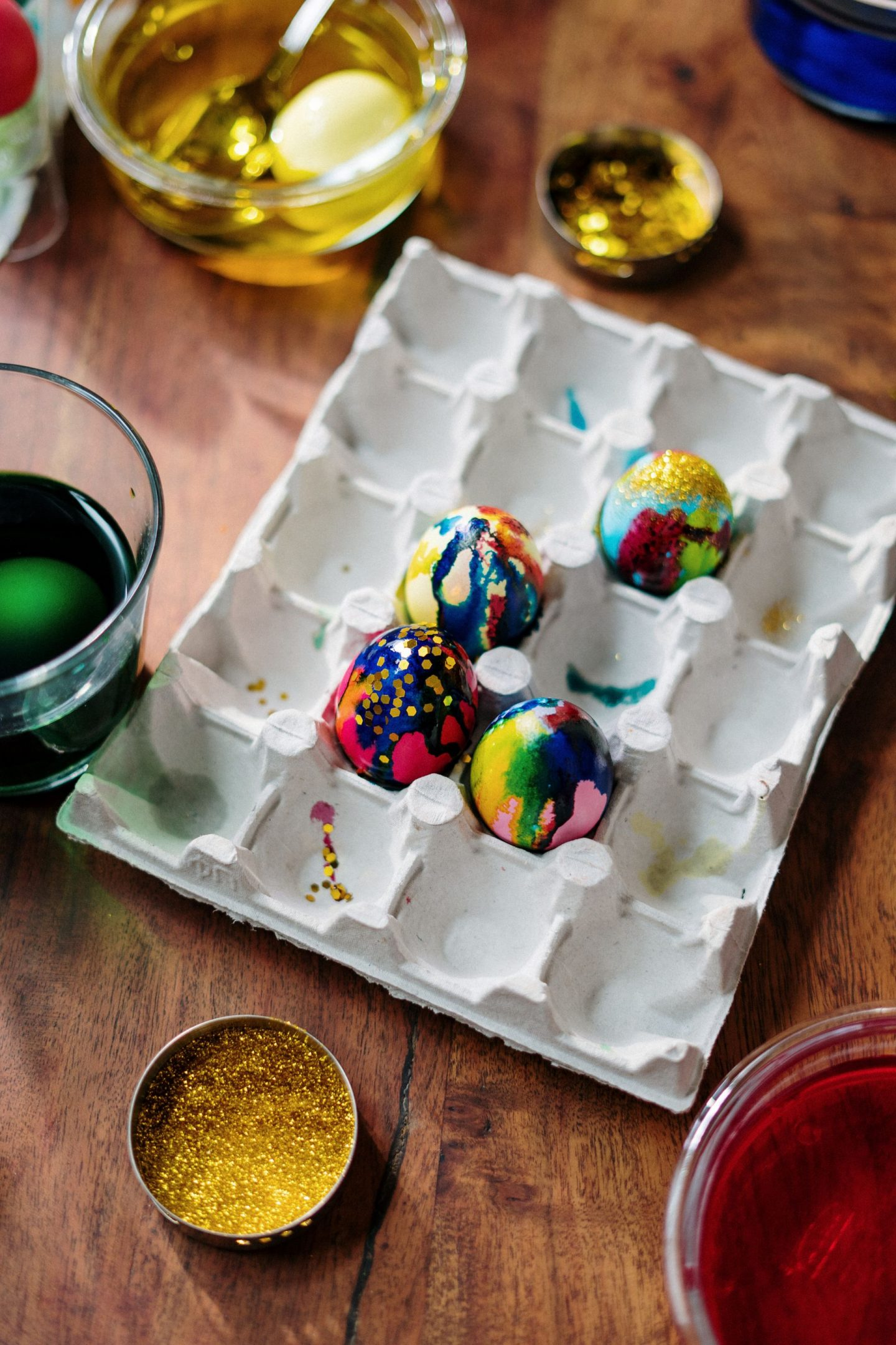 things to do at home during coronavirus: colourful painted eggs surrounded by pots of glitter and paint