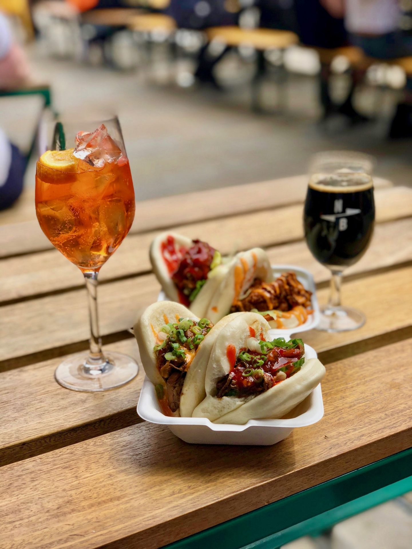 things to do in leeds city centre - bao buns on a takeaway plate on a wooden table outside, with an aperol spritz and a beer alongside