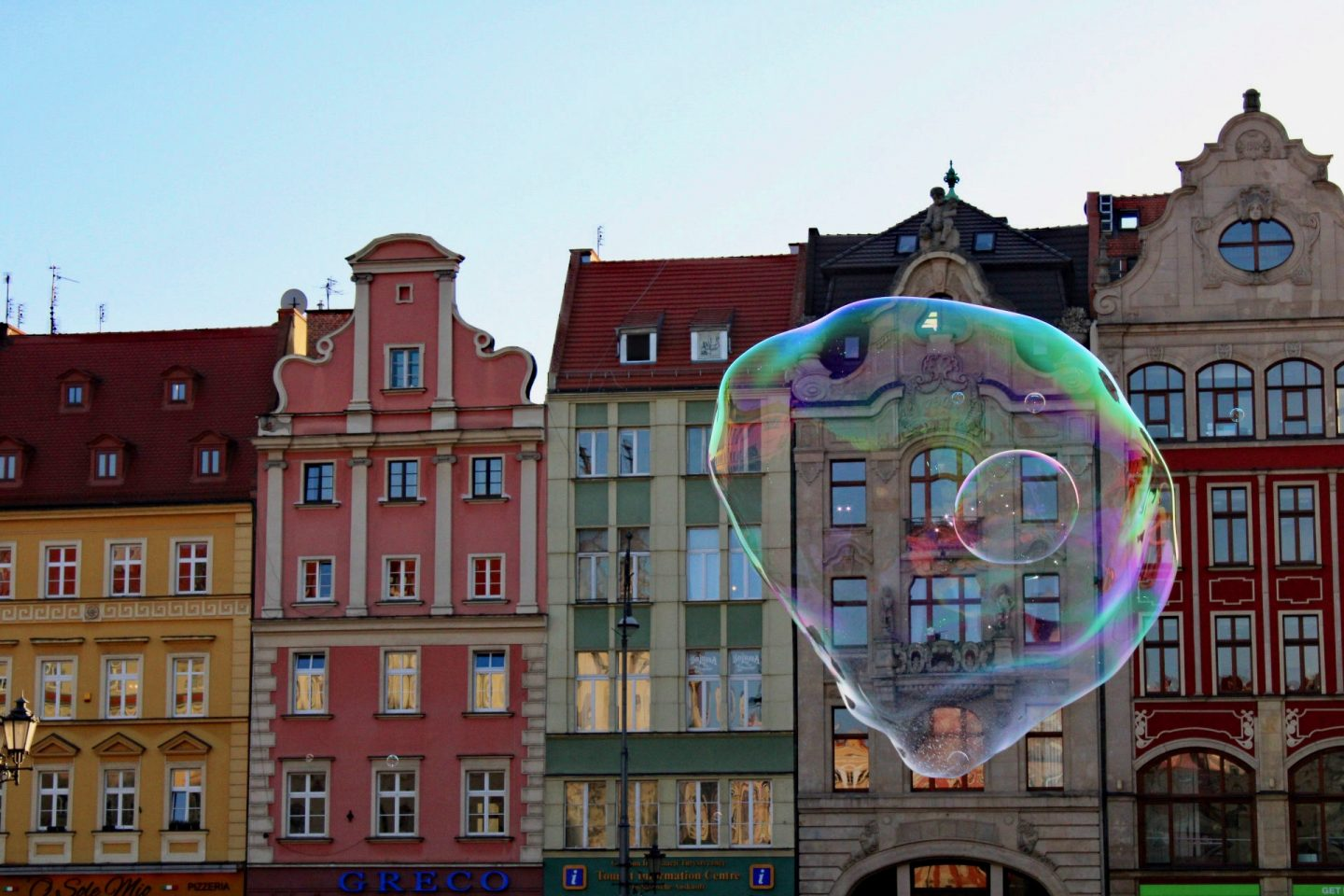 things to do in Wrocław: colourful facades of the market square, with a giant bubble floating in front of them