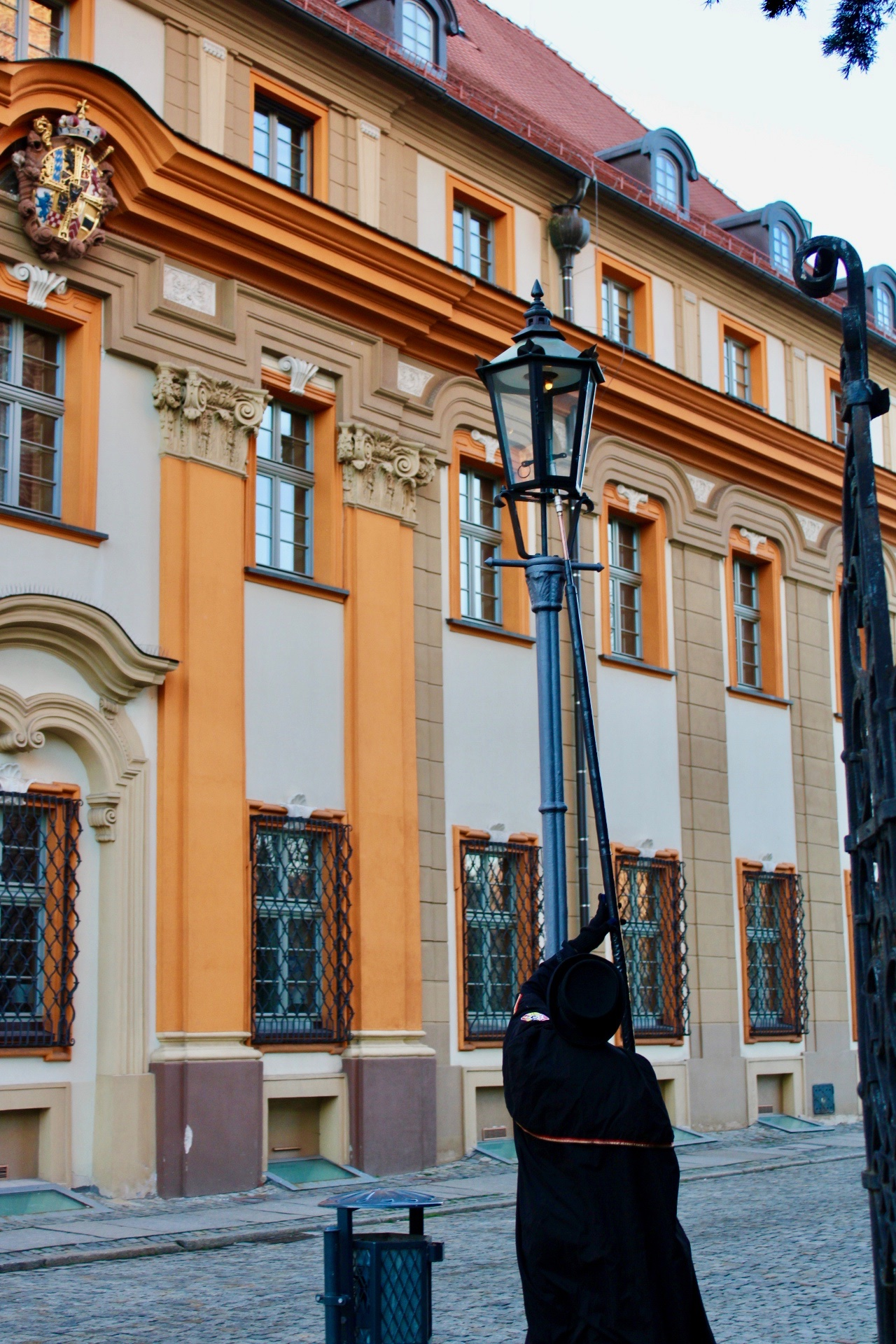things to do in Wrocław: the lamplighter of ostrow tumski lighting a gas-lamp with a long pole