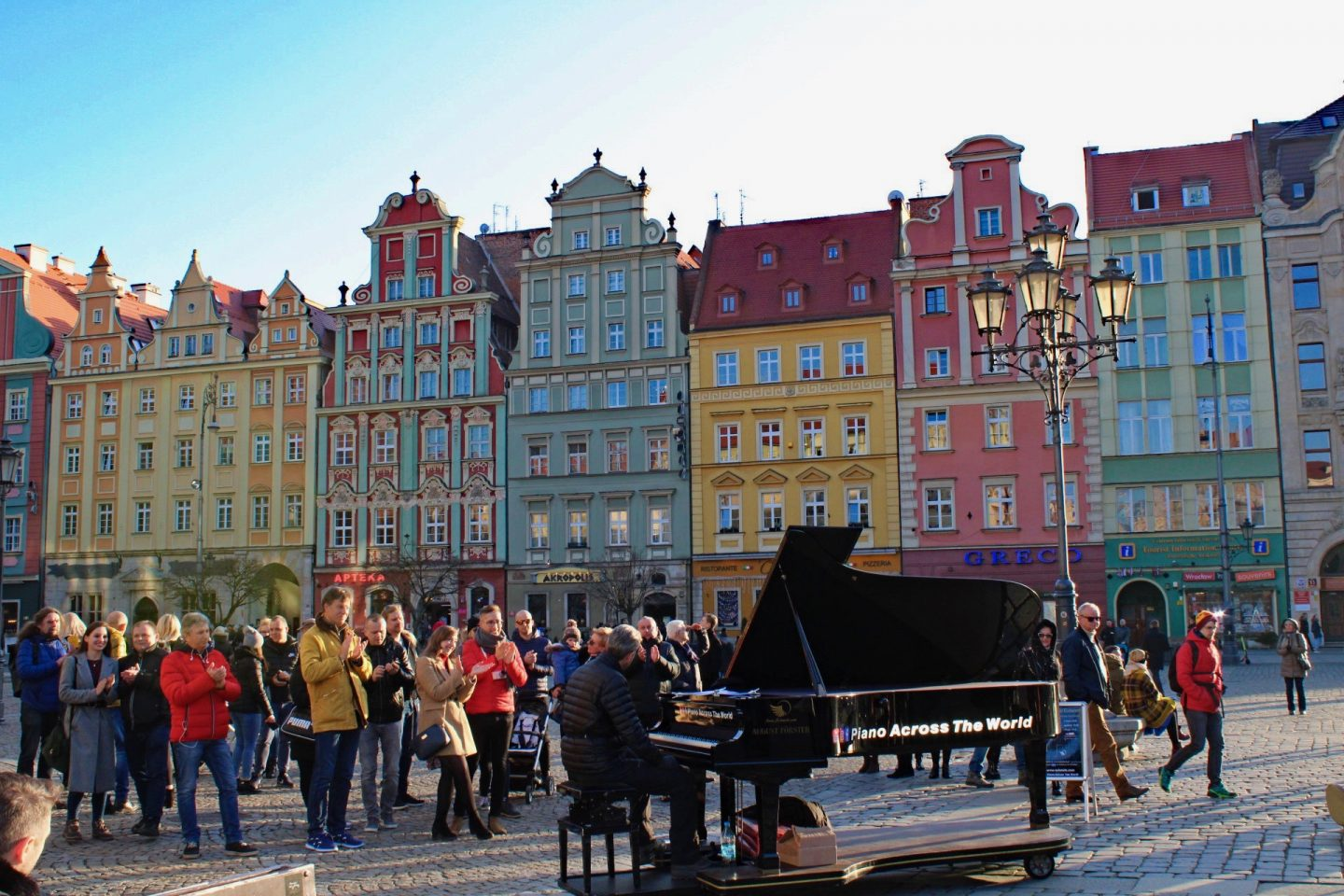 things to do in Wrocław: a man playing the piano in the colourful market square, with a crowd listening and clapping around him