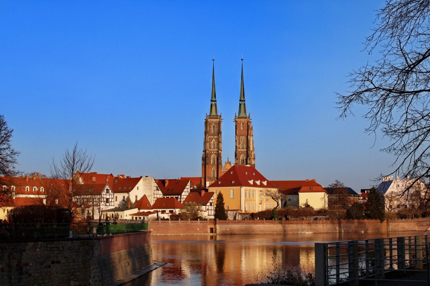 things to do in Wrocław: ostrow tumski across the water in the evening light, with a reflection in the water