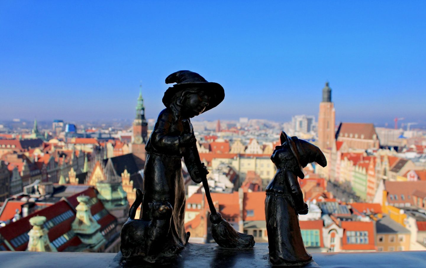 things to do in Wrocław: a small statue of a witch, with views of wroclaw in the background