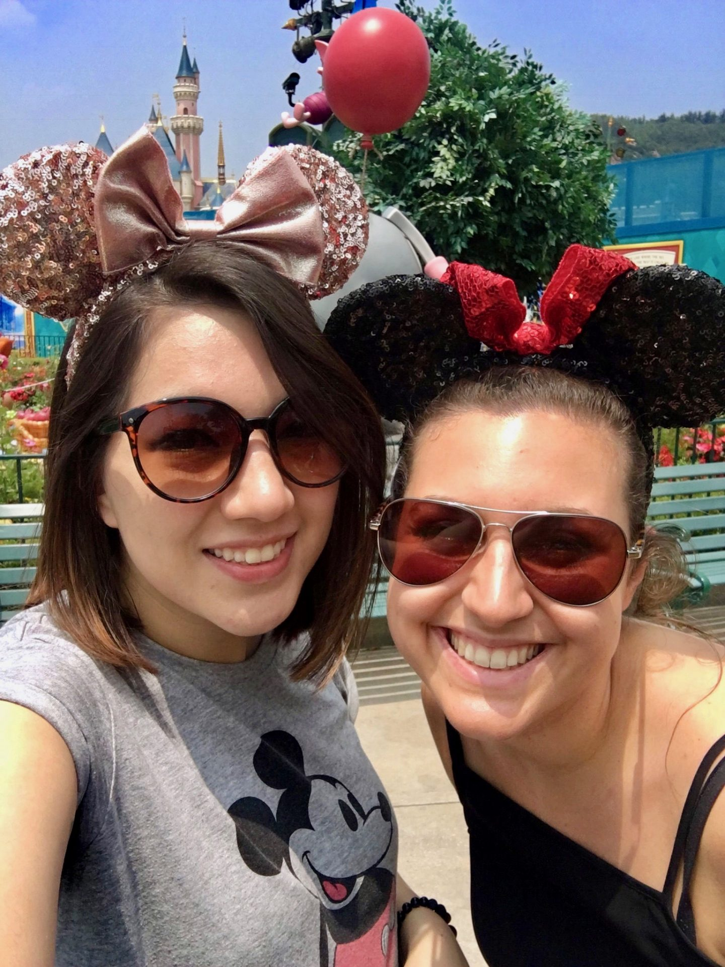 virtual travel experiences: Nell and her friend Aliss at Disney World Hong Kong, wearing mickey mouse eats and smiling at the camera