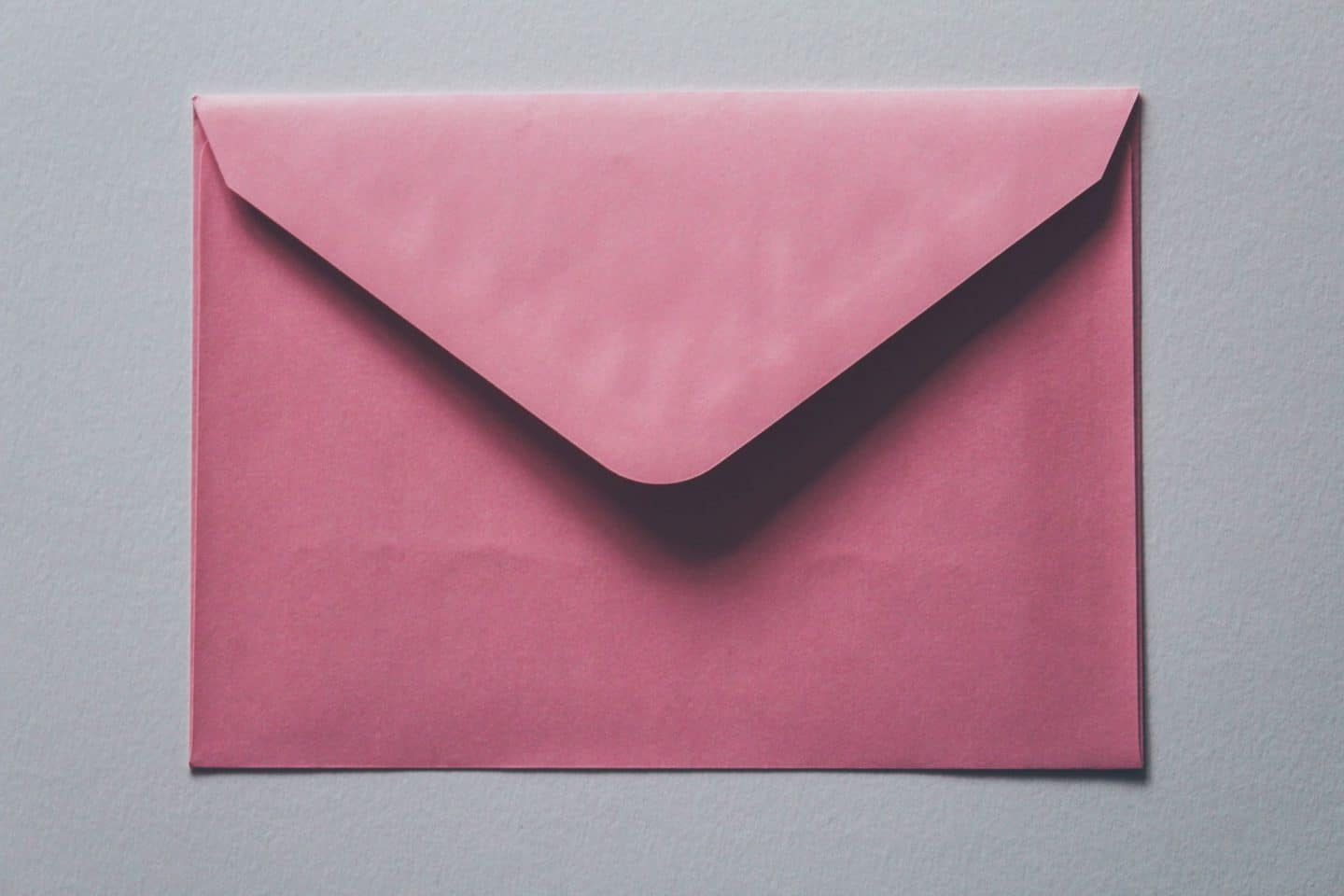 cheer someone up during lockdown: a pink envelope against a grey background