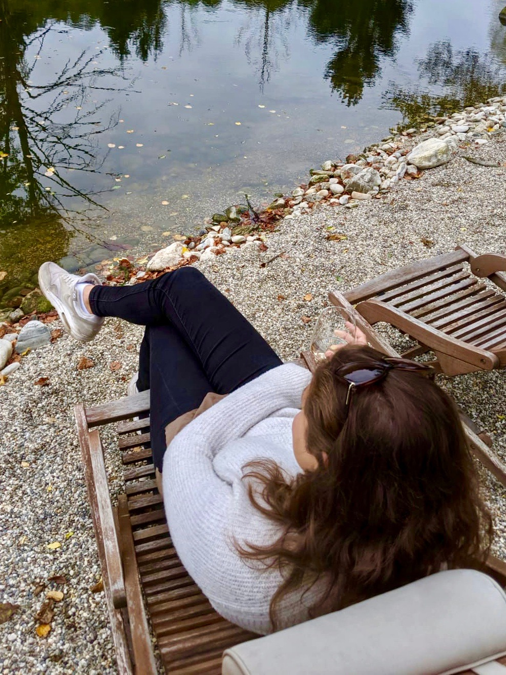 Glamping in Slovenia: Girl sat on deck chair next to pond at Chateau Ramšak vineyard