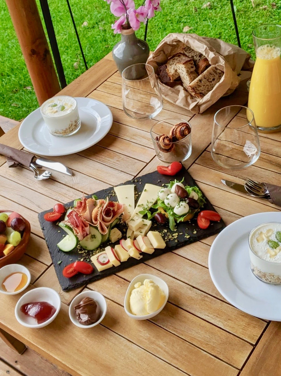 Overhead view of breakfast on wooden table. In the centre is a slate with cheese, ham and salad on. Taken at Chateau Ramsak glamping resort in slovenia