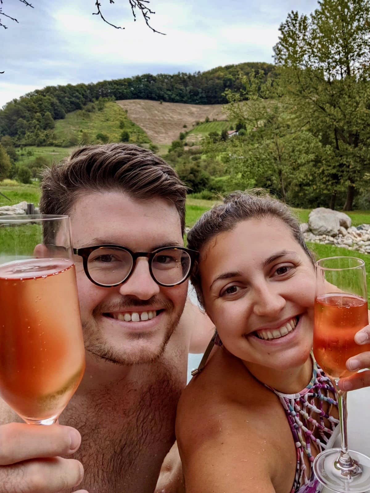 Glamping in Slovenia: A couple holding a glass of rose sparkling wine up and smiling at the camera, with vineyards in the background