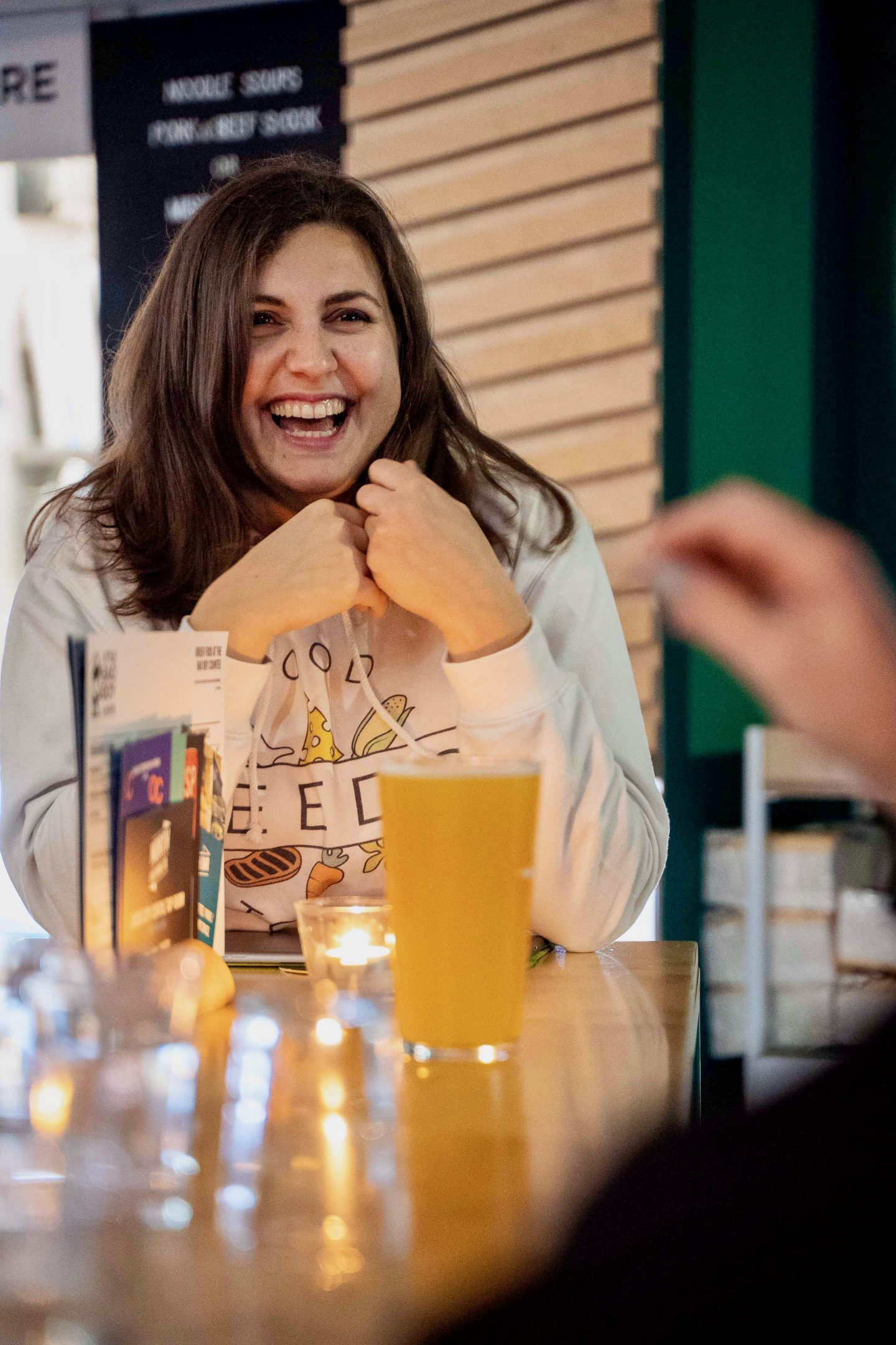 Leeds Food Tours, what to do in Leeds: Nell laughing and looking to the right of the camera, wearing a food tour branded hoodie and laughing