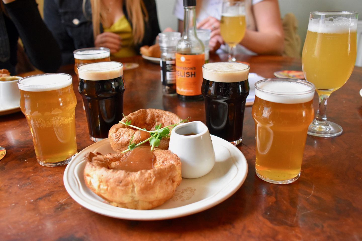 Leeds Food Tours, what to do in Leeds: A plate of Yorkshire puddings surrounded by pints of local beer, on a wooden table