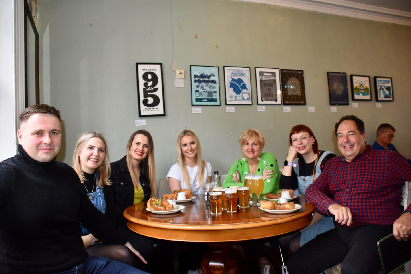 Leeds Food Tours, what to do in Leeds: a group of tour guests sat around a table and smiling at the camera