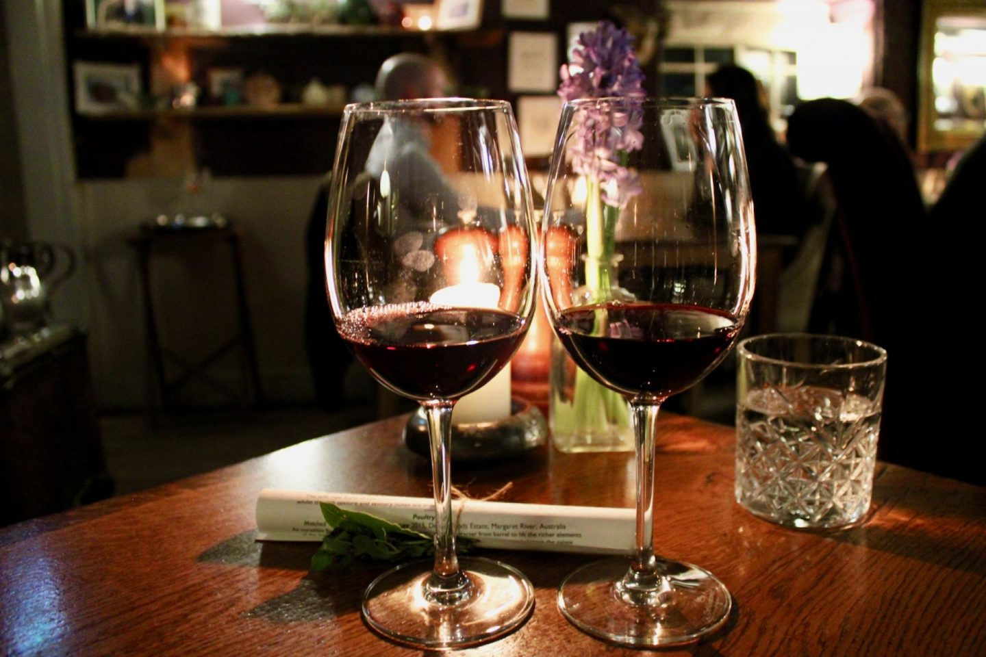 Things to do in Helmsley North Yorkshire: two glasses of red wine on a wooden table, taken at The Star Inn Harome