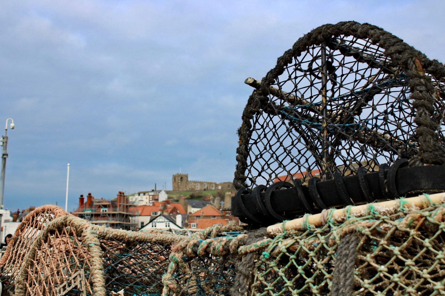 Things to do in Helmsley North Yorkshire: Whitby castle in the background behind some fishing nets
