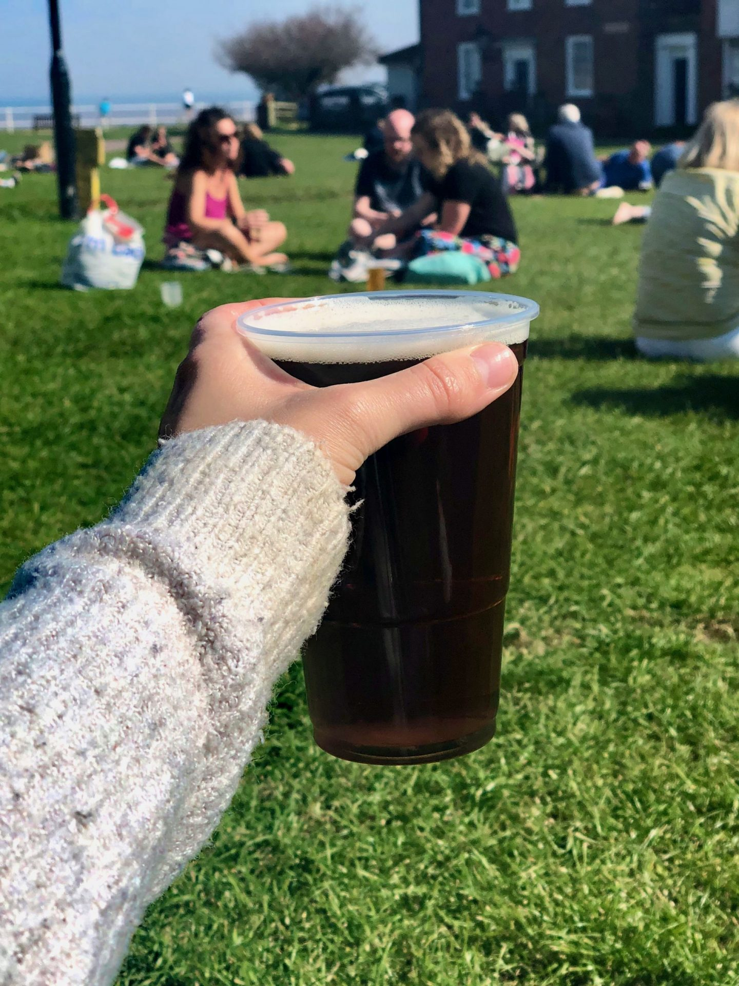 Things to do in Southwold: arm holding a pint of peer in a plastic cup on a green